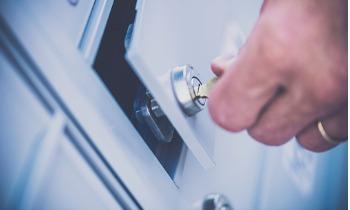 Male hand unlocking door to Carolina Trust safety deposit box picture