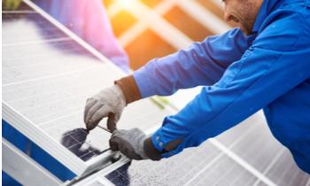 Man installing solar panels onto a roof